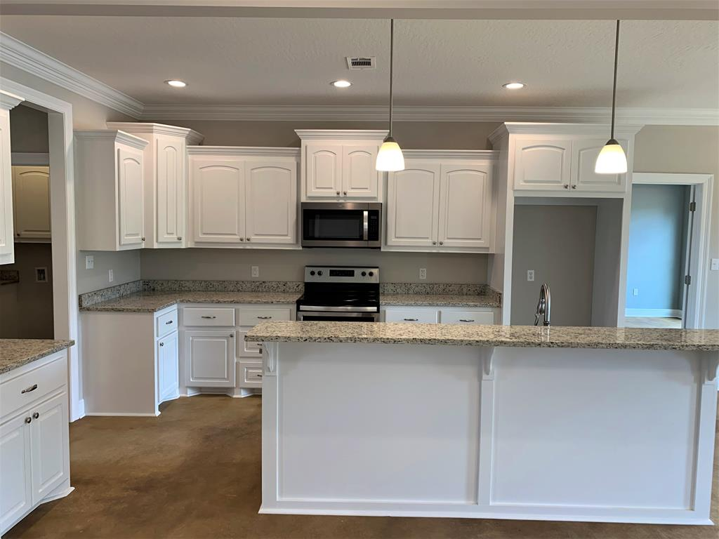 Kitchen has custom cabinetry and granite counter t